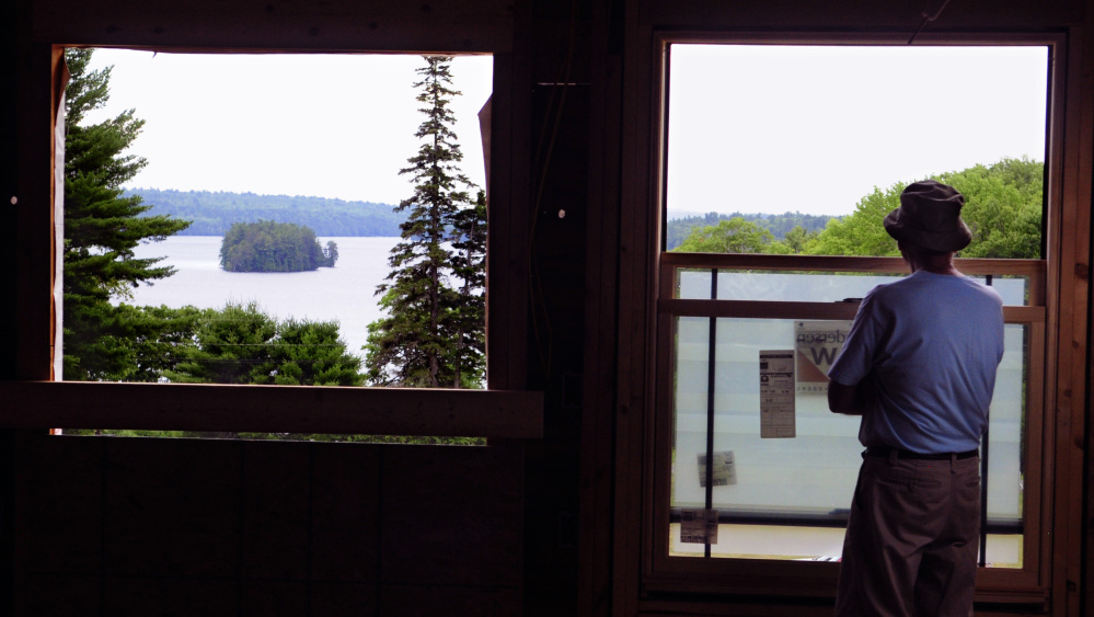During a tour a visitor looks out a second floor window at Long Pond on Saturday at the Travis Mills Foundation's Maine Chance Lodge in Mount Vernon and Rome.