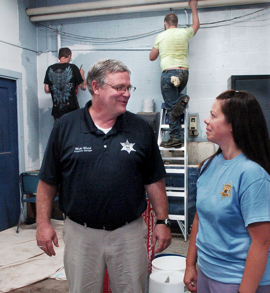 Somerset County Jail Programs Manager Mike Welch speaks with Community Corrections Program Manager Teresa Brown as participants in a community service program paint walls at Madison Junior High School on July 17.