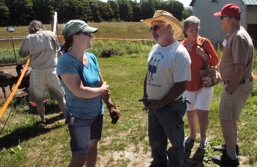Emu farmer Richard Merrow speaks with Michelle Wynn about raising the birds at the Birds of a Feather Farm in Farmington on Sunday during this year's statewide Open Farm Day.