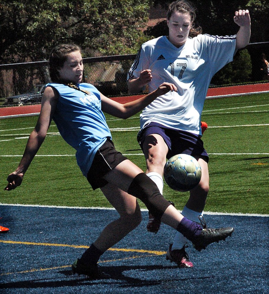 Staff photo by David Leaming Waterville's Lily Foster, left, and Mt. Blue's  Miranda Nicely battle for possession during a benefit soccer game at Colby College on Sunday to honor former Messalonskee student Cassidy Charette.