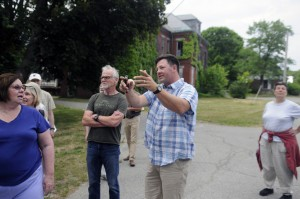 Matt Morrill, center, describes to several residents what he would like to do with the buildings at the Stevens School complex in this June file photo.