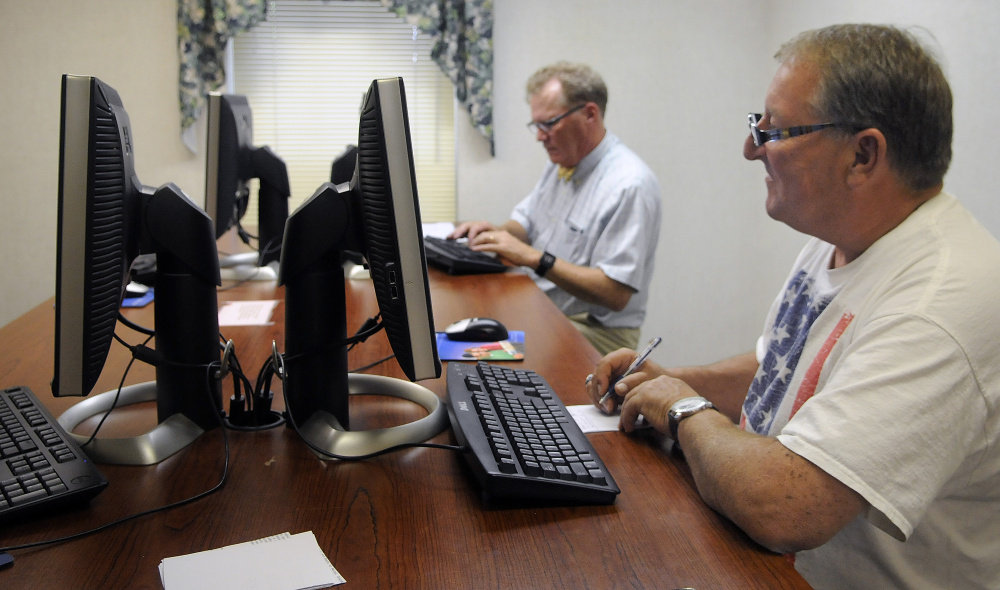 Walter Stanley, right, of Connecticut, and Gardiner attorney Bruce Williams research deeds Monday at the Kennebec County Registry of Deeds, which recently relocated to 77 Winthrop St. in Augusta.