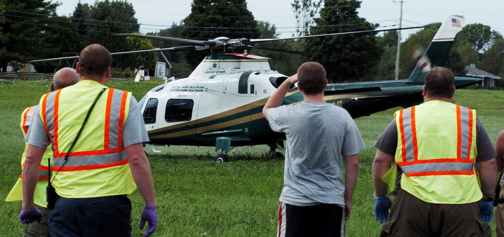 Fairfield first responders watch as a Lifeflight helicopter lands in a field near a car accident scene Monday on Center Road. Jeff Neill, of Fairfield, was taken to Central Maine Medical Center in Lewiston with serious injuries.