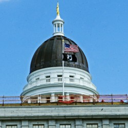 A fence rings the roof of the Senate wing of the State House on Tuesday in Augusta, where a crew is replacing decorative ledges and fixing the roof.