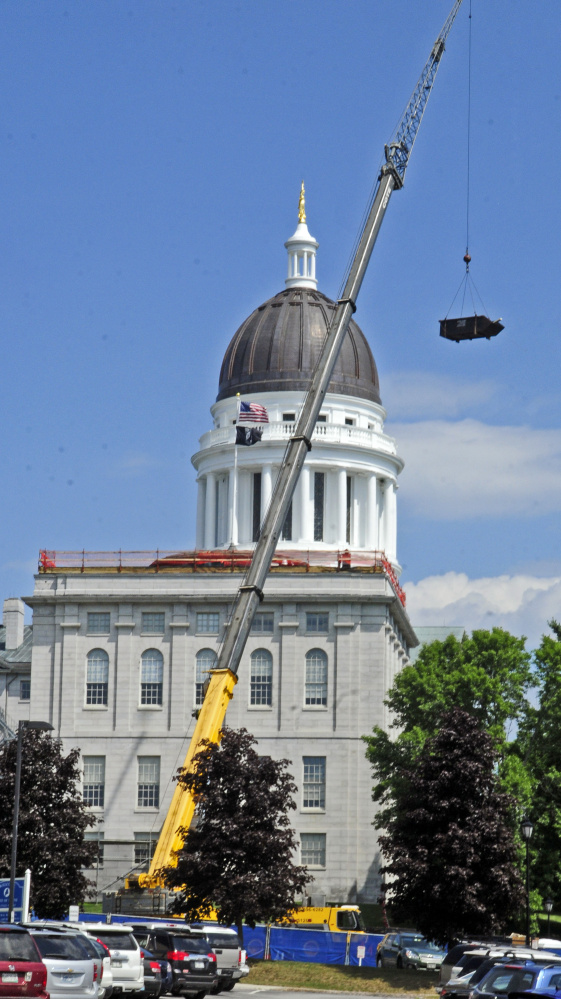 A crane lowers a dumpster off the roof of the Senate wing of the State House on Tuesday in Augusta, where workers are making repairs.