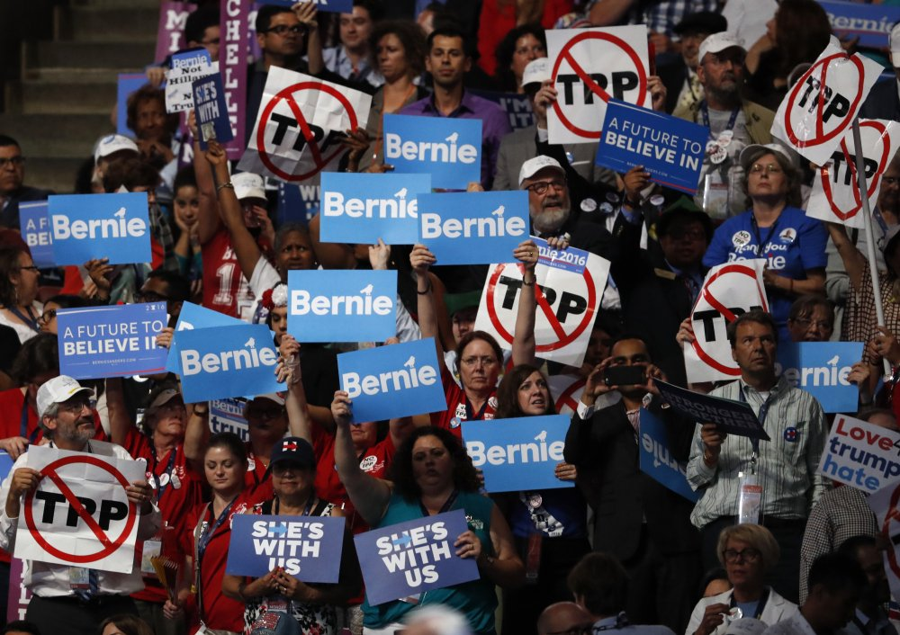 Bernie Sanders supporters hold signs, including those critical of the Trans-Pacific Partnership, or TPP, during the first day of the Democratic National Convention in Philadelphia on Monday.