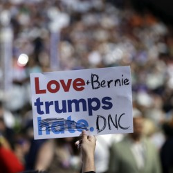 "A delegate holds up a sign during the first day of the Democratic National Convention in Philadelphia on Monday. Several delegates supporting Bernie Sanders on Monday took campaign signs that read ""Love trumps hate"" and modified them to instead read ""Love + Bernie trumps DNC"" or ""Love Bernie or trump wins."""