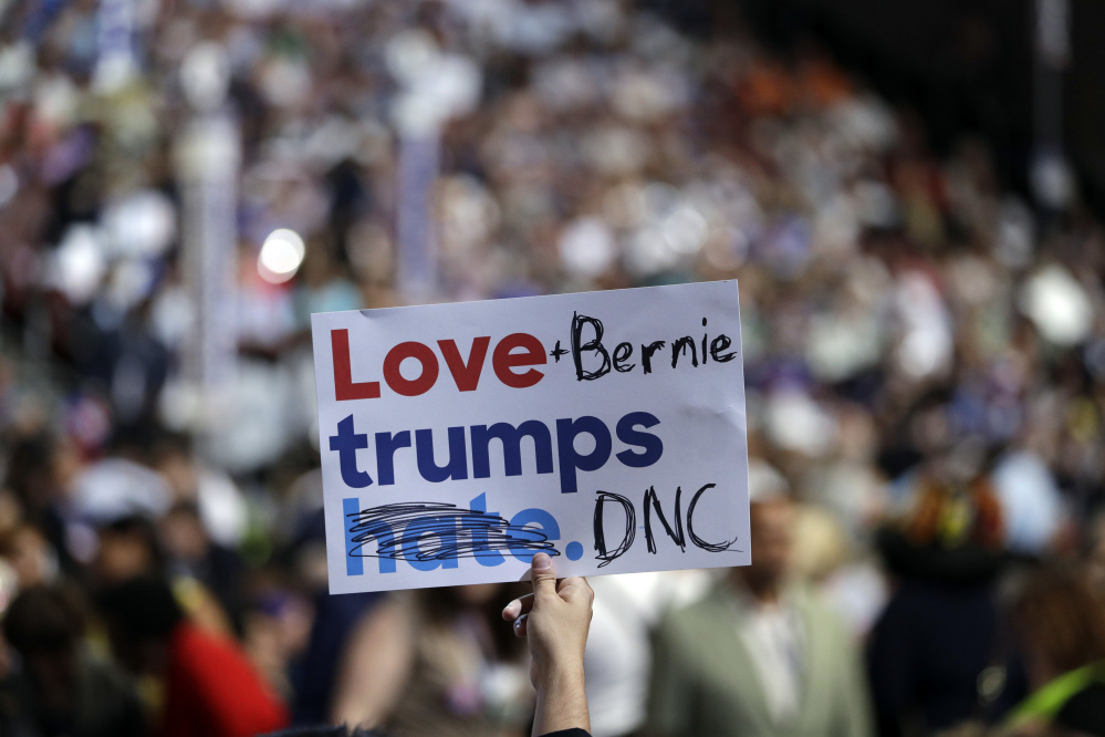 """A delegate holds up a sign during the first day of the Democratic National Convention in Philadelphia on Monday. Several delegates supporting Bernie Sanders on Monday took campaign signs that read """"Love trumps hate"""" and modified them to instead read """"Love + Bernie trumps DNC"""" or """"Love Bernie or trump wins."""""""