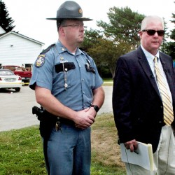 Maine State Police Lt. Brian McDonough, center, speaks about a possible home invasion Thursday that resulted in the death of one man and serious injuries to two others at the home, which stands in the background off Main Street in Rangeley. Maj. Brian Scott, left, and Rangeley police Chief Russell French attended the news conference.
