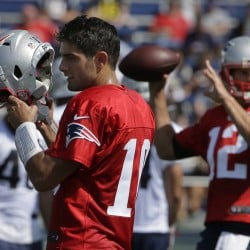 New England Patriots quarterback Jimmy Garoppolo, left, removes his helmet as quarterback Tom Brady, right, winds up for a pass during training camp Thursday in Foxborough, Massachusetts.