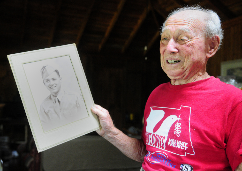 Holding a picture of himself after being discharged from U.S. Army, Alfred Jacobs, 92, talks about serving in World War II on Tuesday during an interview at his summer home in Readfield.