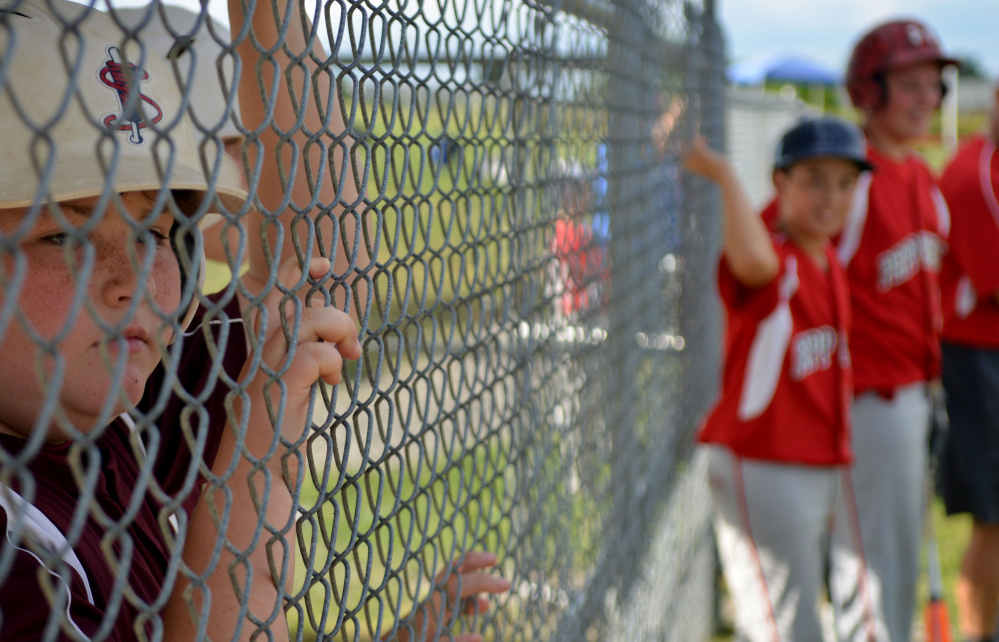 Jake Hayes, 11, from Chelmsford, Massachusetts, far left, watches the Cal Ripken U12 home run derby at Carl Wright Complex in Skowhegan on Friday.
