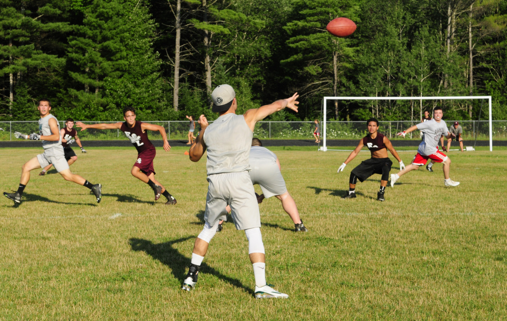 Winthrop/Monmouth slot back Nate Scott, center, throws a pass to Kane Gould during a 7-on-7 game against Edward Little on Friday in Turner.