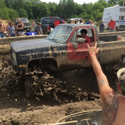 """Spectators cheer as a pickup truck splashes through mud at an event formerly called the Redneck Olympics on Saturday in Hebron. The organizer now calls the event the """"Redneck (Blank)"""" after Olympic officials complained about the name."""