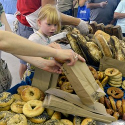 Francis DeGeer helps her mother, Marcia, and father, Derek, fill orders of bread from their bakery table Hootenanny Bread at the Maine Artisan Bread Fair at the Skowhegan Fair Grounds on Saturday.
