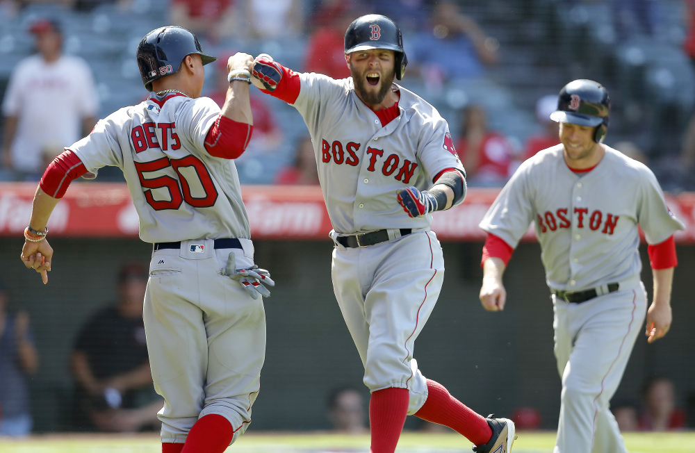 Boston's Dustin Pedroia, center, celebrates with Mookie Betts, left, after hitting a three-run home run to put them ahead of the Los Angeles Angels during the ninth inning Sunday in Anaheim, California. The Red Sox held on to win 5-3.