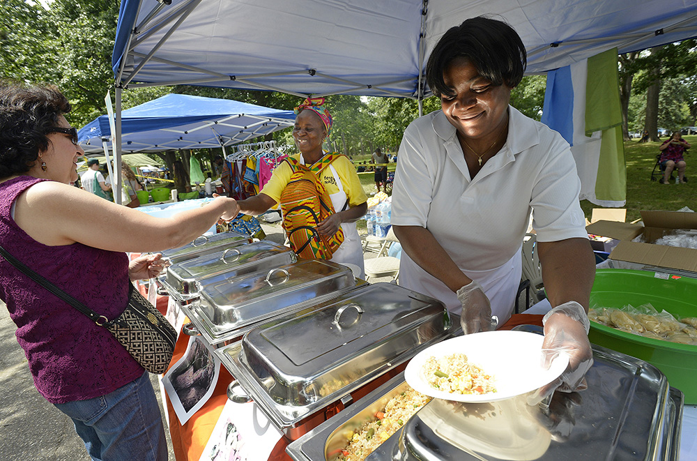 Mavis Kwakutse, right, of Scarborough, who is originally from Ghana, loads a plate of food for Leticia Foss of Sanford, who is originally from Mexico, during the Festival of Nations at Deering Oaks in Portland on Saturday. In the background collecting money is Kadiatu Moriba of Portland, who grew up in Sierra Leone. Shawn Patrick Ouellette/Staff Photographer