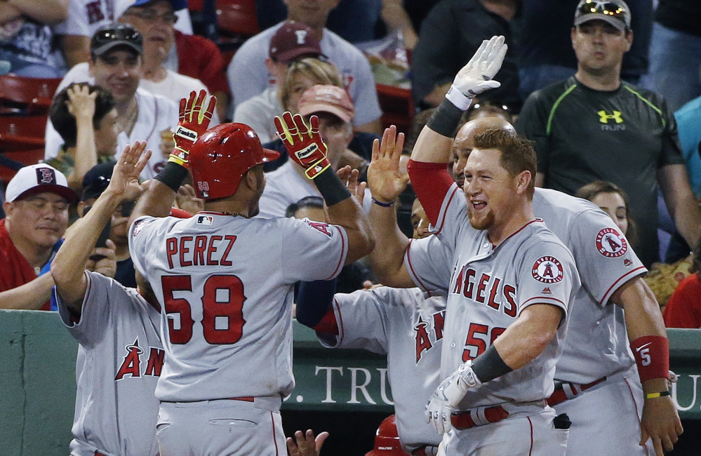 Carlos Perez of the Los Angeles Angels is welcomed by teammates Saturday night after hitting a two-run homer in the seventh inning of the 21-2 win over the Boston Red Sox.