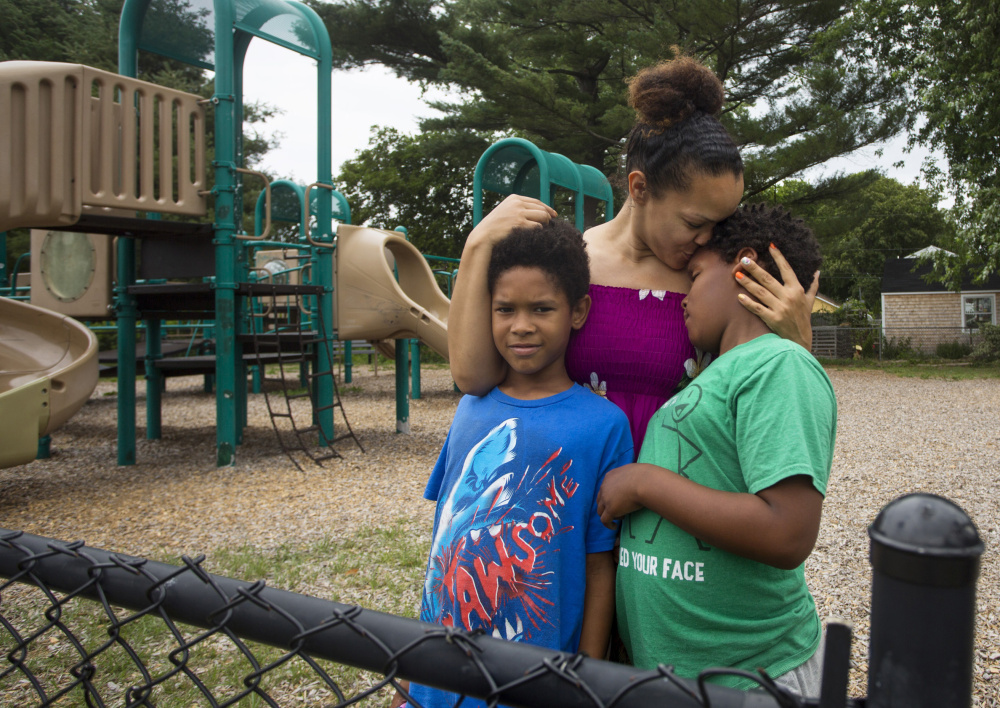"""Marion Sloan has recently found herself having discussions with her sons David Quashie, left, and Dhyomie Quashie about how to act around police officers. """"I told them, 'They're not all bad. You just need to make sure your behavior is correct,' """" Sloan said."""