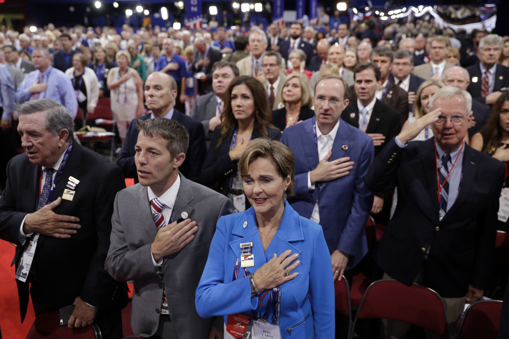 Alabama delegate Judy Carns, center in blue, and other delegates put their hands on their chests as they sing the national anthem during first day of the Republican National Convention in Cleveland, Monday, July 18, 2016.