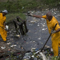 Brazilian sanitation workers remove garbage collected by floating waste barriers in the Meriti River, which flows into Guanabara Bay, where sailing races are scheduled to be held at next month's Summer Games in Rio de Janeiro. Associated Press/Silvia Izquierdo