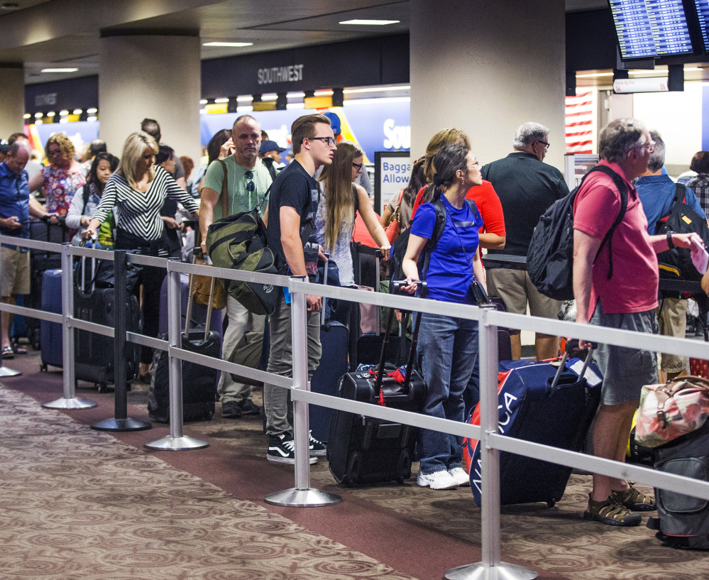 Passengers wait in the Southwest Airlines check-in line at Sky Harbor International Airport in Phoenix on Thursday, after one of the largest disruptions in the airline's history.