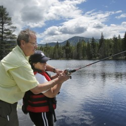 Bruce Albiston helps Hazel Hanscom cast while fishing near Sugarloaf Mountain in Carrabassett Valley on Tuesday. Albiston and his wife, Annemarie, have founded the Adaptive Outdoor Education Center, which provides opportunities for people with disabilities to participate in outdoor activities.