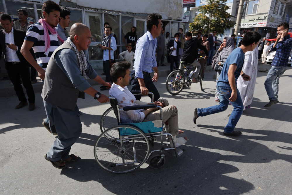 Afghans help an injured man at a hospital after an explosion struck a protest march in Kabul, Afghanistan, on Saturday.