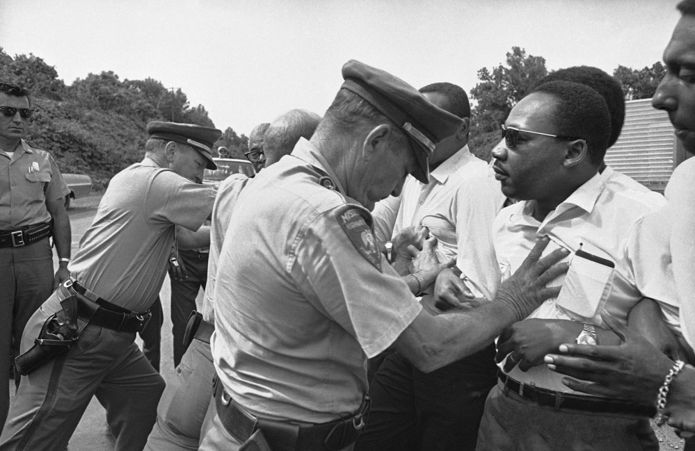FILE - In this June 7, 1966 file photo, Mississippi Highway Patrolmen shove the Rev. Martin Luther King and members of his marching group off the traffic lane of Highway 51 south of Hernando, Miss. King, Student Non-Violent Coordinating Committee leader Stokely Carmichael (head visible at upper right) and other civil rights leaders had taken up the march begun by James Meredith. (AP Photo)