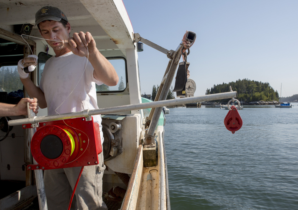 Bryan Kelley uses an automatic jigging machine he's testing as part of a project with The Nature Conservancy.