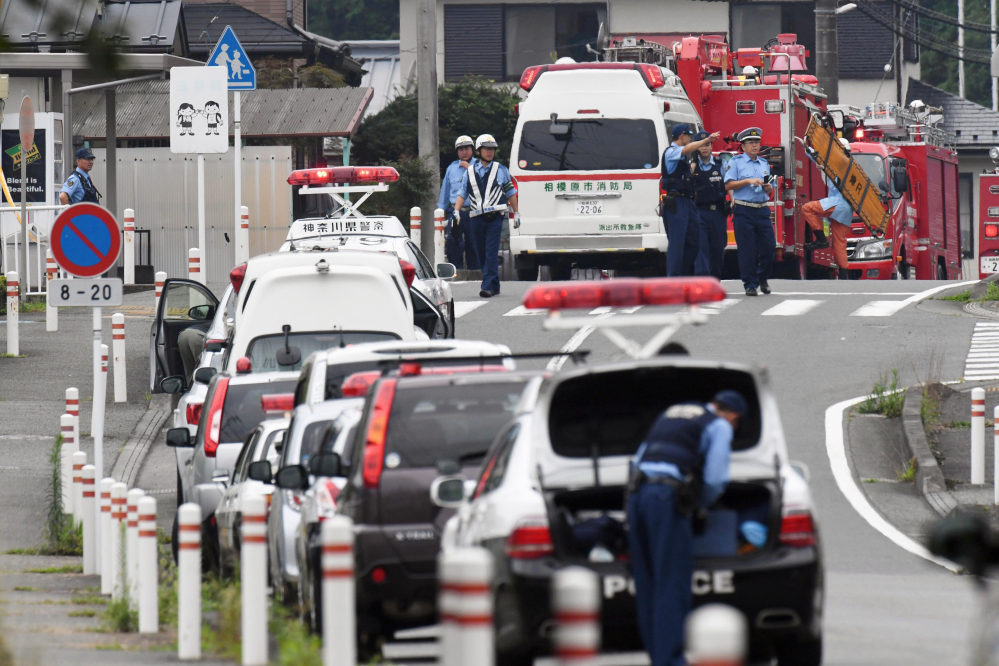 Police officers stand by with ambulances and firetrucks on a street near a facility for the handicapped where a number of people were killed and dozens injured in a knife attack Tuesday in Sagamihara, outside Tokyo.