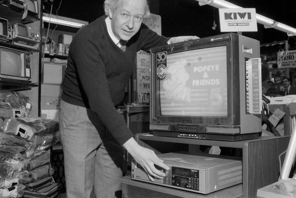 A salesman shows how to tape from TV to Toshiba video cassette recorder in 1984. Funai Electric Co. makes the world's last video cassette recorder. And now it won't.
