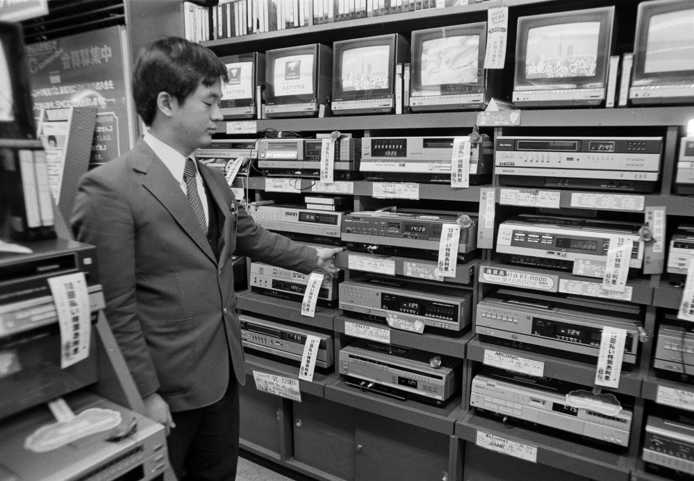 In this Dec. 15, 1981, file photo, a sales clerk at an electronics store in the Akihabara District of Tokyo, displays a stack of video cassette recorders which are on sale for 20 to 30 percent off. Japanese electronics maker Funai Electric Co. says it's yanking the plug on the world's last video cassette recorder. A company spokesman, who requested anonymity citing company practice, confirmed Monday that production will end sometime during the month, although he would not give a date.