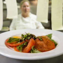 A line cook reads new meal tickets at the Woodlands Club kitchen in Falmouth after plating this tomato caprese salad with pistachio-encrusted goat cheese.