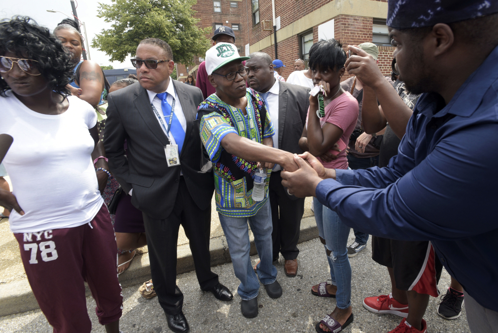 Elder C.D. Witherspoon, right, shakes the hand of Freddie Gray's father Richard Shipley, center, as Gray's mother Gloria Darden, left, and twin sister Fredericka Gray, second from right, stand nearby after a news conference held by Baltimore State's Attorney Marilyn Mosby Wednesday.