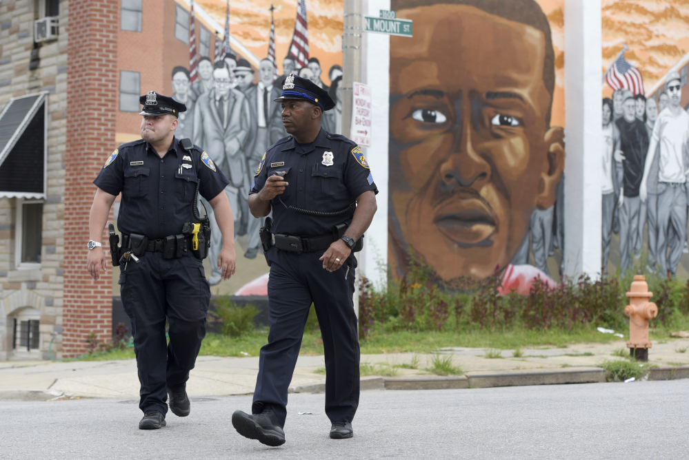 Baltimore police walk near a mural depicting Freddie Gray after prosecutors dropped remaining charges against the three Baltimore police officers who were still awaiting trial in Gray' death. The decision by prosecutors comes after a judge had already acquitted three of the six officers charged in the case.