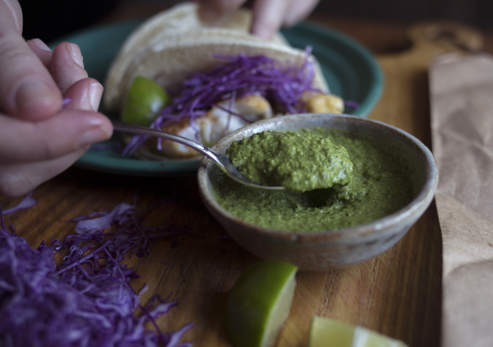 Christine Burns Rudalevige scoops cilantro-and-corn pesto onto fish tacos.