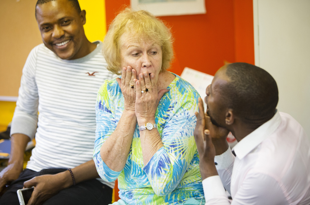 Congolese immigrant Serge Betu Muambi, left, listens as Jacqueline Webb of Poland and Roger Mwamba make whooping sounds, a Congo custom, to celebrate Christelle Kasongo's birthday during a meeting last month of the Hillview Adult French Club in Lewiston. The club gathers immigrants from French-speaking countries and Maine residents who want to keep their French language active.