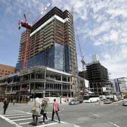 In this Thursday, May 19, 2016, photo, passers-by walk near the construction site a high-rise building in Boston. On Friday, July 29, 2016, the Commerce Department issues the first estimate of how the U.S. economy performed in the April-June quarter. (AP Photo/Steven Senne)
