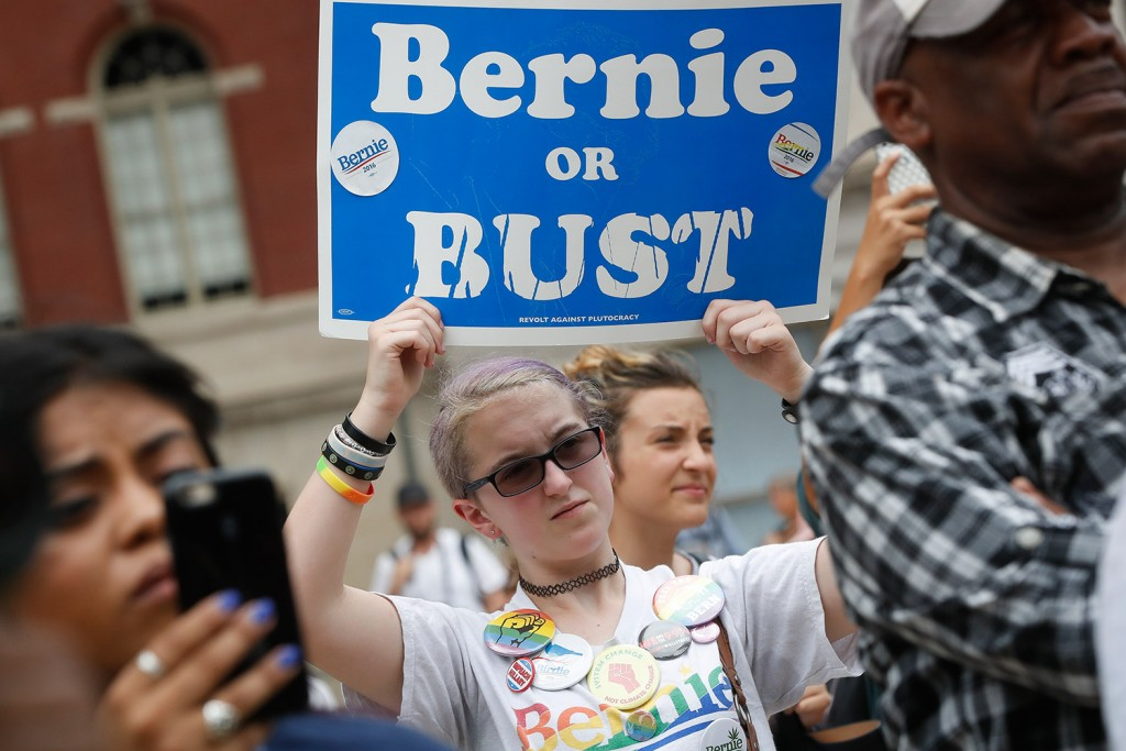 """A supporter of Sen. Bernie Sanders, I-Vt., holds a """"Bernie or BUST"""" sign at a rally in Philadelphia on Thursday during the final day of the Democratic National Convention."""