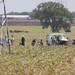 """The partial frame of a hot air balloon is visible at the scene in a field near Lockhart, Texas, where a hot air balloon carrying at least 16 people collided with power lines Saturday, causing what authorities described as a """"significant loss of life.""""   Ralph Barrera/Austin American-Statesman via AP"""