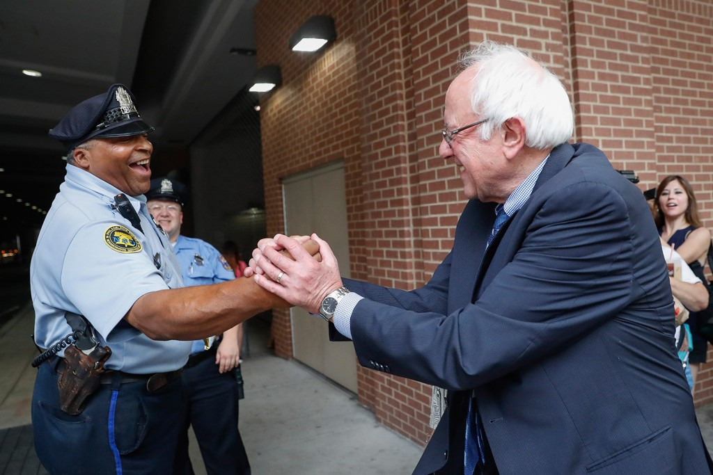 Sen. Bernie Sanders, I-Vt., right, greets a police officer during walk around downtown in Philadelphia on Thursday during the final day of the Democratic National Convention.