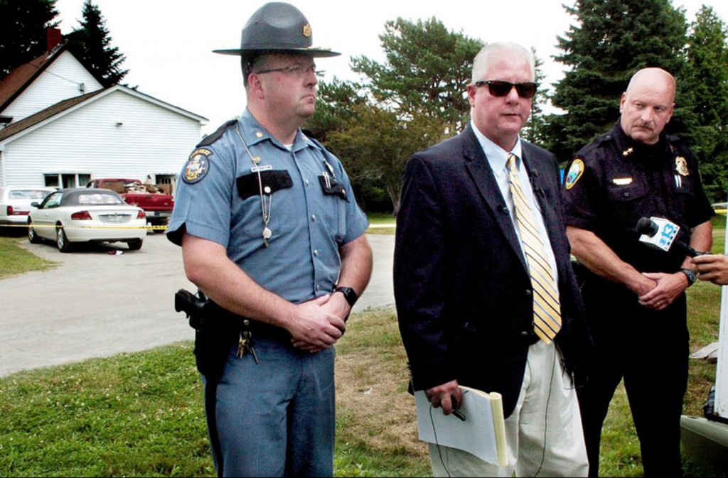 Maine State Police Lt. Brian McDonough, center, speaks about a possible home invasion Thursday that resulted in the death of one man and serious injuries to two others at the home in background off Main Street in Rangeley. At left is Maj. Brian Scott and at right is Rangeley Police Chief Russell French.