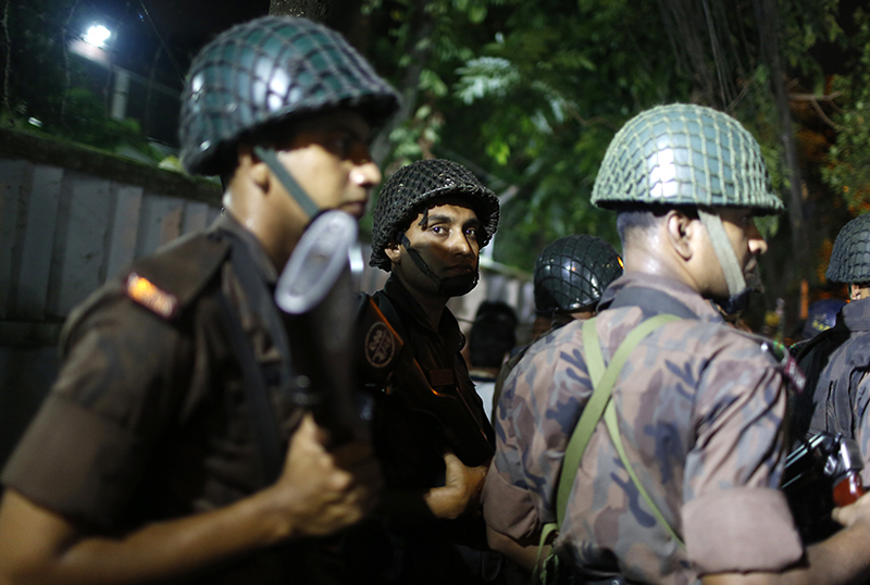 Bangladeshi security personnel stand guard near the Holey Artisan Bakery restaurant in Dhaka.