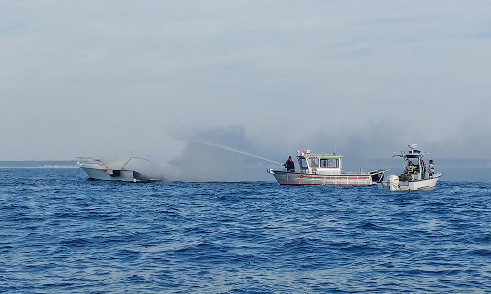 Saco Fire Department personnel attempt to extinguish the boat fire Tuesday morning.