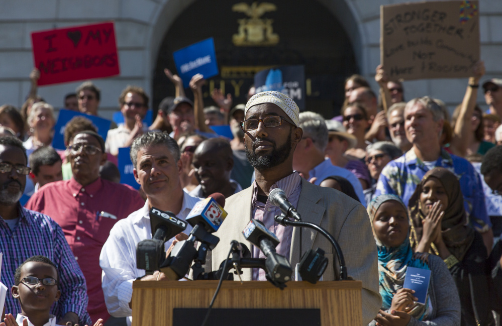 Mahmoud Hassan, president of the Somali Community Center of Maine, pauses for applause during a rally at Portland City Hall to protest Thursday's comments by Republican presidential nominee Donald Trump. Ben McCanna/Staff Photographer