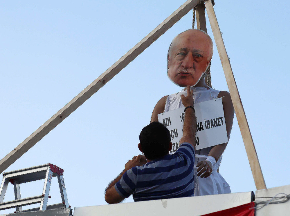 A man attaches an image to create an effigy of Fethullah Gulen – who is accused of being behind the July 15 coup – on a makeshift gallows at in Ankara, Turkey, on July 29.