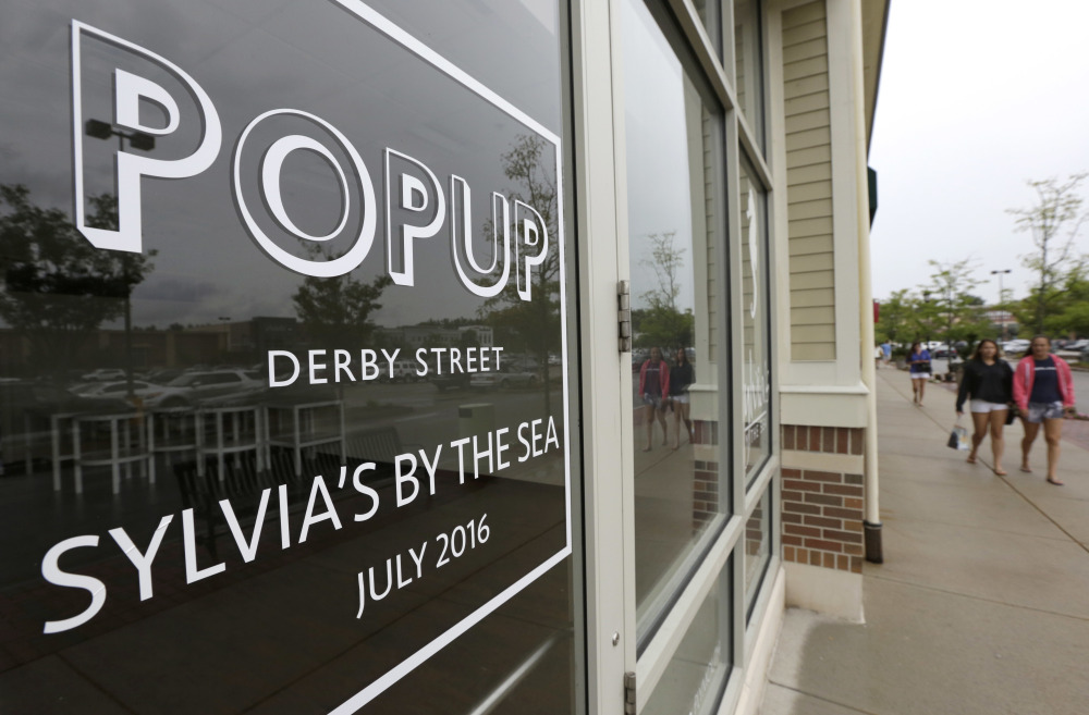 """People walk past the entrance of a pop-up store location at the Derby Street Shoppes outdoor mall in Hingham, Mass., on Tuesday. Entrepreneurs increasingly are taking the """"pop-up"""" concept in new directions."""