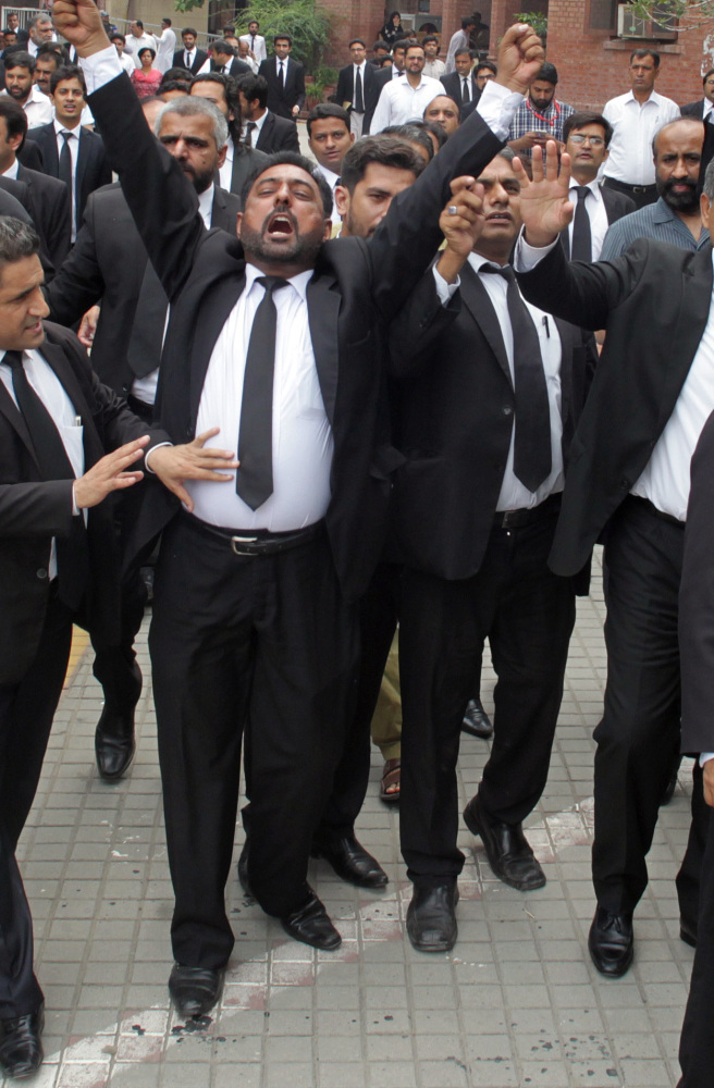 Pakistani lawyers hold a demonstration to condemn a suicide bombing in Quetta that killed dozens of people and wounded many more in Lahore, Pakistan, Monday.