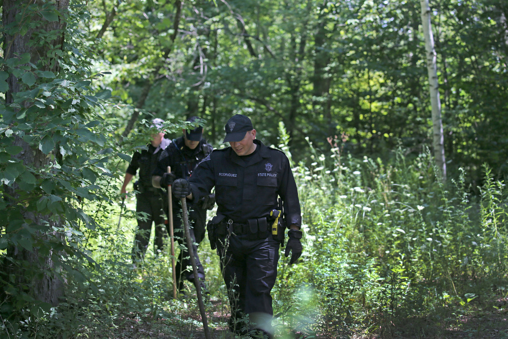 Massachusetts State Police search the woods for evidence after a woman visiting her mother was found slain Tuesday in Princeton, Mass., after she went out for a run.